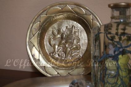 Piatto in ottone con decorazione realizzata a sbalzo e cesello. Fichidindia e torre normanna.