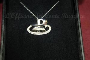 Tre lettere, P M G che insieme formano una barca d'oro e diamantini. Ciondolo progettato da Mirko Noto e realizzato dal maestro orafo Giuseppe Amodeo