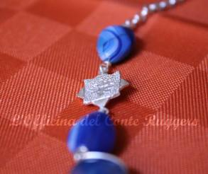 Particolare in agata blu e argento 925 a forma di stella ad 8 punte con decorazione floreale realizzata a sbalzo e cesello